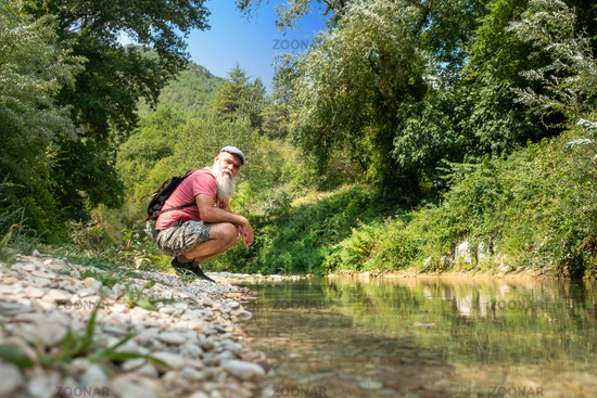 Hiker is resting by the stream