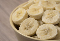 Sliced banana in ceramic bowl on wooden background. Close up.
