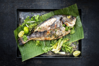 Fresh barbecue gilthead seabream with lettuce and herbs as top view on a green banana leaf