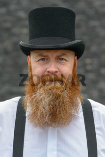Middle-aged bearded man in top hat and braces