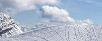 Panoramic view on off piste slope for freeriding with traces from skis, snowboards