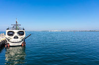 Pleasure boat at the pier. The stern of the ship is framed in the shape of a human skull.