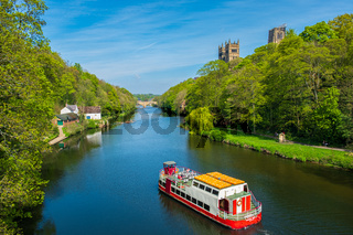 A cruise boat cruises along River Wear on a beautiful spring day in Durham, United Kingdom