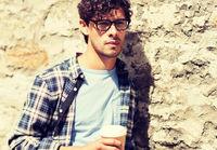 man in eyeglasses drinking coffee over street wall