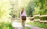 woman riding bicycle with basket at summer park