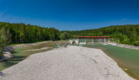 A sandbank in front of the isar river and a weir.