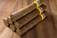 rolled cigars from a tobacco leaf on a wooden background, Small depth of sharpness