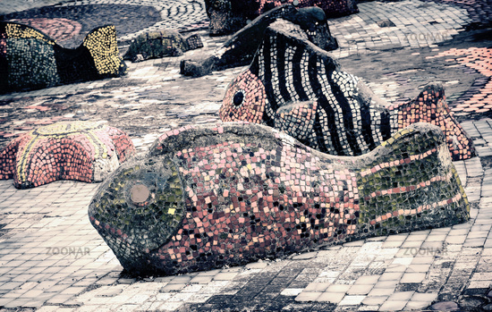Mosaic sculptures of fish near the pond.