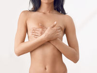 Torso of a slender middle-aged naked woman in panties