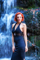 Young woman stands in front of a waterfall