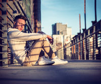 Handsome trendy young man, sitting on a sidewalk in city