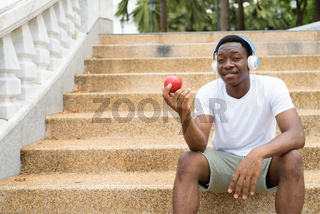 African man listening music with headphones and holding red apple
