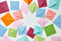 Colorful frame from empty handmade envelopes on a light background.