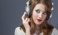 Teenager, redhead girl with helmet on her head listening to music on a flat gray background