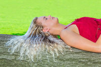 Young woman with long hair lies on tree trunk