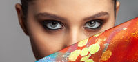 beautiful girl eyes and makeup next to a colored silk cloth
