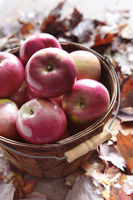 Red apples in wooden basket with fall leaves