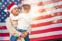 Hispanic Male Soldier Wearing Santa Cap Holding Mixed Race Son In Front of American Flag