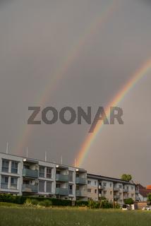 doppelter Regenbogen bei einem Gewitter ueber Wohnhaus - Hochformat