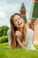young beautiful woman laughing lies on a green lawn