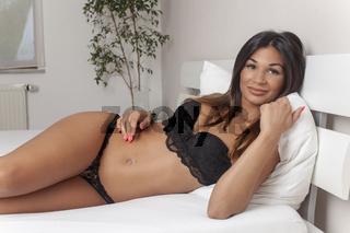 Brünette Frau im Bett liegend