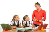 Girls at their desks have fun watching their beloved teacher