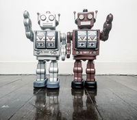 two vintage robots say hi  on a wooden floor toned