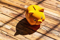 Yellow piggy bank casts a shadow