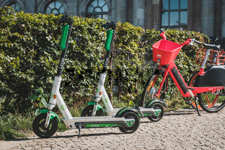 Electric E scooter , escooter or e-scooter and bike sharing bicycle on sidewalk in Berlin