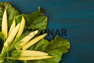 CORN IN BEET LEAF ON A WOODEN BOARD. YOUNG YELLOW EARS OF CORN IN GREEN LEAF BEETS ARE DARK BLUE WOODEN BACKGROUND. ORGANIC CEREAL.
