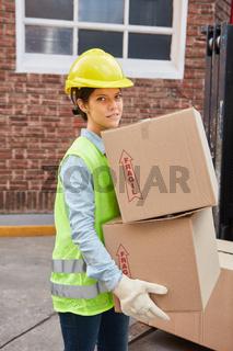 Frau als Lagerarbeiter transportiert Pakete