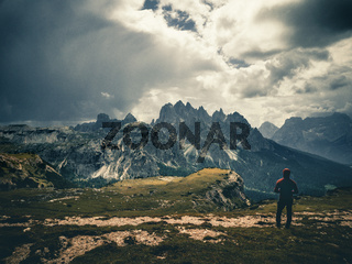 young man enjoying the view of the mountains landscape in the dolomites mountain range.