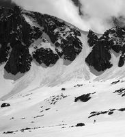 Black and white high mountains with snow cornice and avalanche tracks