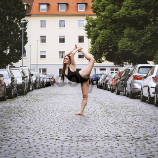 carefree young woman ballet dancer exercising on city street