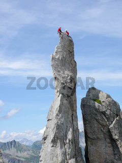rock climbers sitting  on top a sharp rock needle in the Val Bregaglia