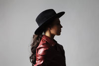 brunette woman wears a black hat and a leather jacket