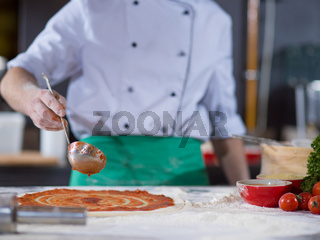 Chef smearing pizza dough with ketchup