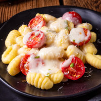 gnocchi baked with green pesto, cherry tomatoes and parmesan
