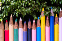 Unusual bright colour fence made of tall big pencils outdoors