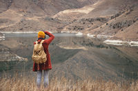 A portrait from the back of a girl traveler take a picture on the background of a lake in the mountains in autumn or early spring. Travel concept