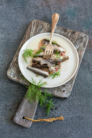 Salted spicy anchovies in oil with dill and pepper.