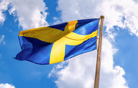 Swedish flag blue with yellow cross waving in the wind