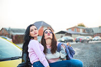 Best female friends cheering by car road trip at sunset. Happy people outdoor on vacation tour