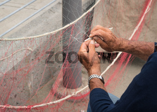 Old fisherman is fixing a fishing net