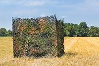 Camouflage tent in dutch grain field