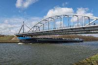 Ship at Dutch Amsterdam Rijn canal passing a steel bridge