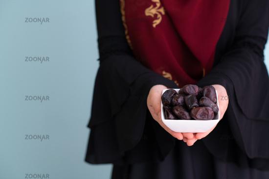 modern muslim woman holding a plate of dates in ramadan kareem
