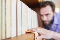 Hausmann beim Staub wischen an Bücherregal