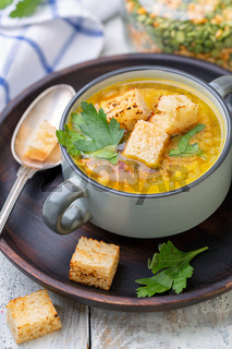 Pea soup with smoked ribs and croutons in a bowl.