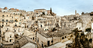Panoramic view of Matera (Sassi di Matera) with its steep ancient stone streets, European Capital of Culture 2019, with clouds, at southern Italy, waiting to welcome tourists.